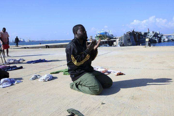A man prays in a navy base in Tripoli after his boat sank off the coast of Libya in December.