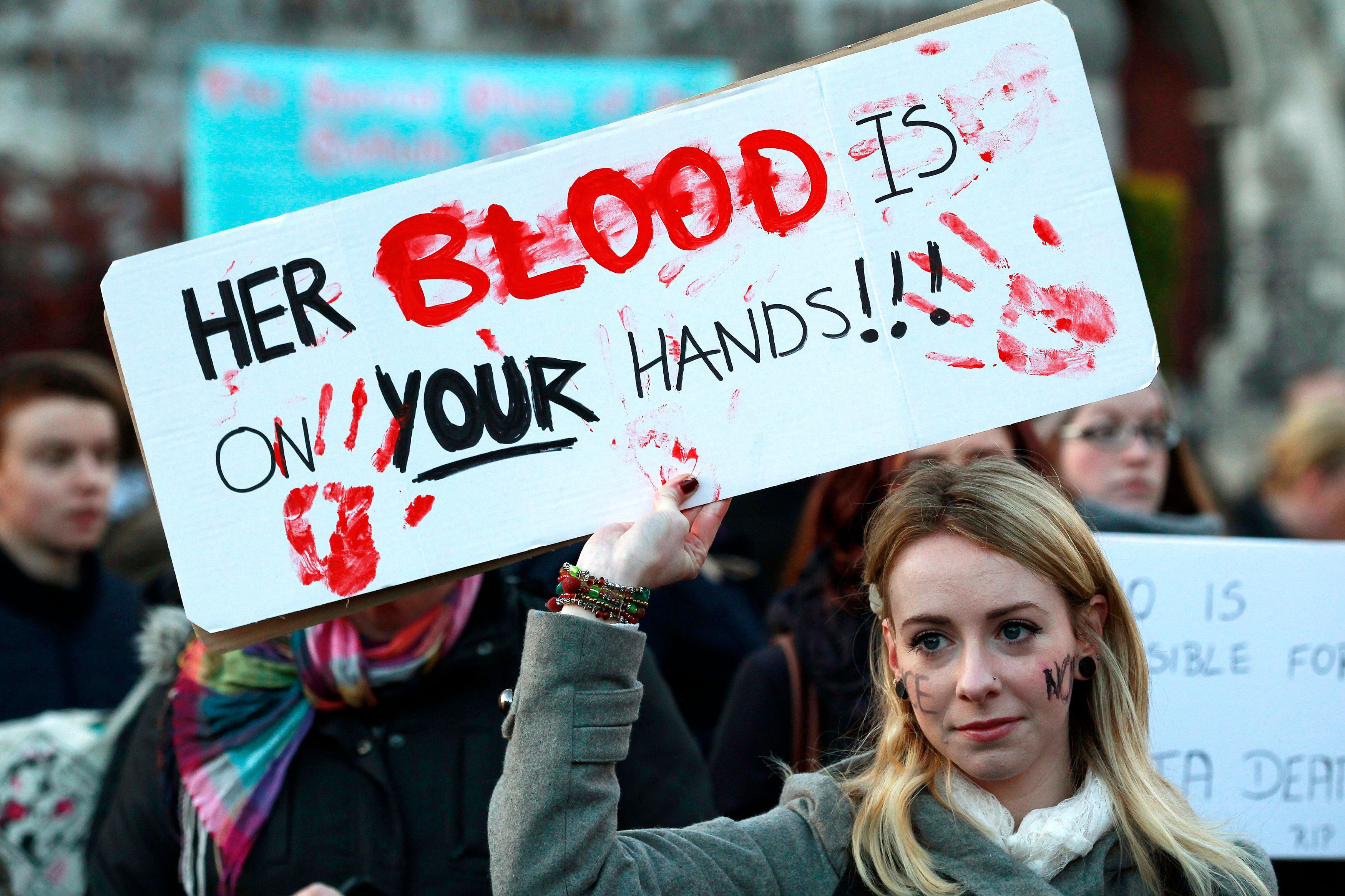 A woman holds a poster during a vigil in November 2012 in Dublin in memory of Savita Halappanavar, who died of septicemia fol