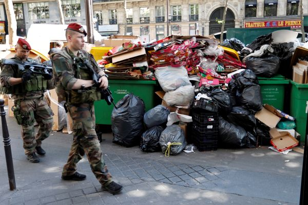 Soldiers pass by a pile of rubbish bags on the Grands Boulevards.