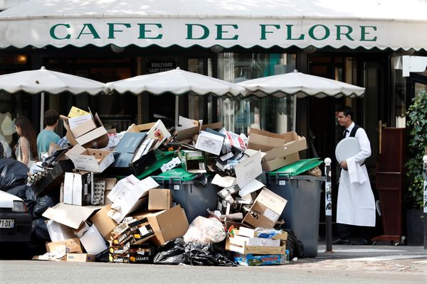 A waiter stands near a pile of garbagebags in front of the Cafe de Flore on Wednesday.