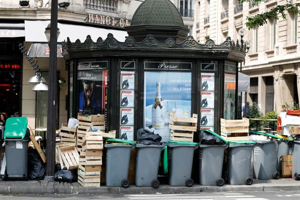 Garbage containers and rubbish bags surrounda Parisian kiosk selling newspapers and magazines.