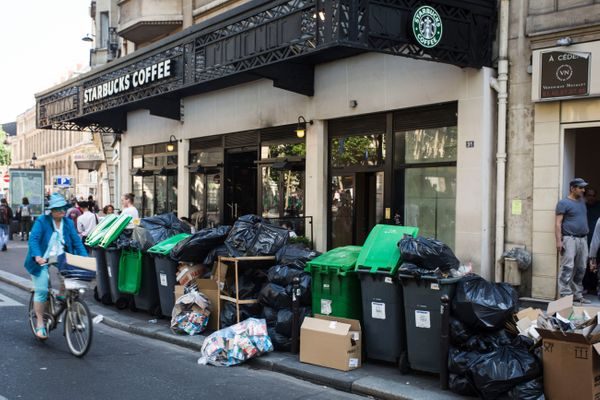 A woman rides a bicycle pastpiles of garbage in central Paris.