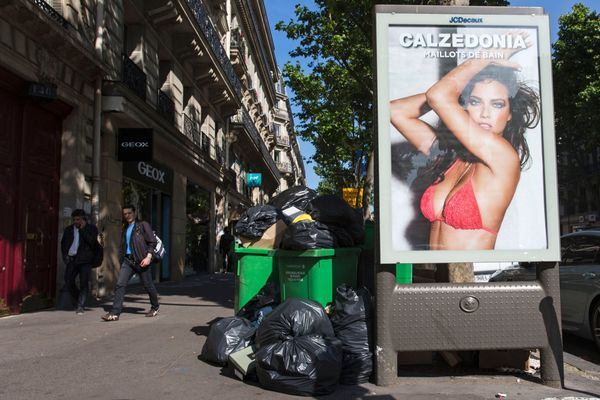 Pedestrians pass piles of garbage in central Paris.