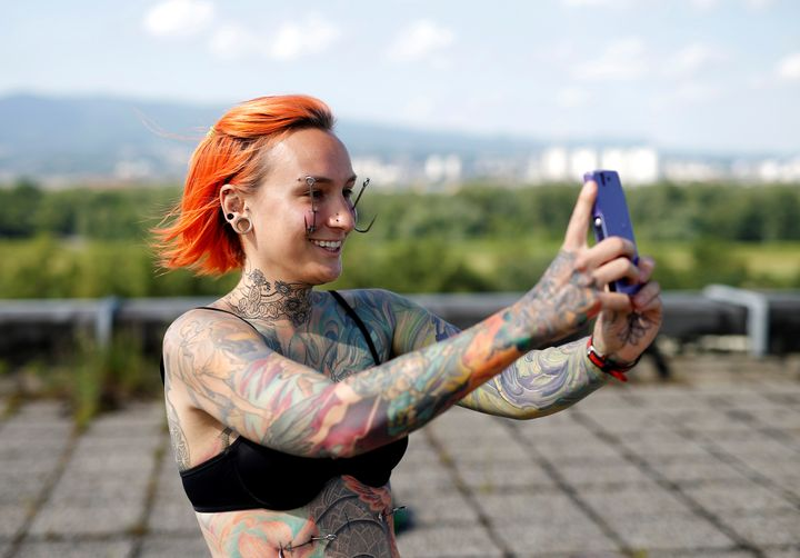 Kaitlin, 28, from the United States takes a selfie as she waits to be suspended by the professional body artist Dino Helvida.