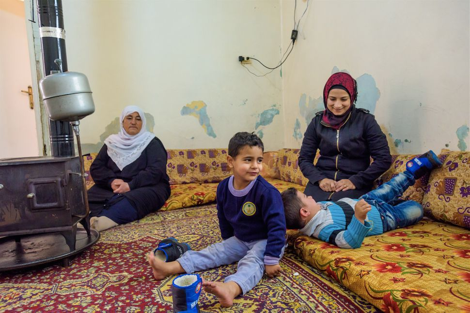 Haisha with her mother-in-law Fatima, and twoof her fourchildren. Her son Jamal (in the blue striped sweater) has