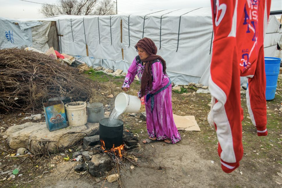 Woman preparing a pot of boiling water for laundry, in the Bekaa Valley, Lebanon.