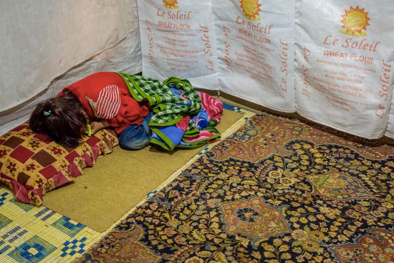 A child refugee lying on a makeshift bed in her home in the Bekaa Valley.