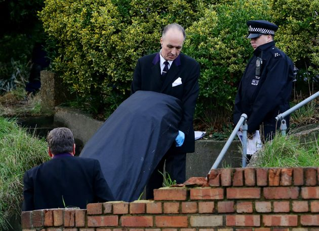 Police remove one of the bodies from the family home in Erith,