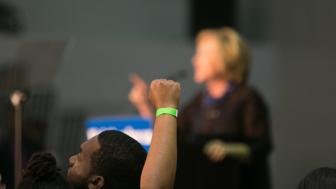 ATLANTA, GA - OCTOBER 30: A protester with the ''Black Lives Matter'' movement throws a fist up as Democratic presidential candidate, Hillary Clinton, speaks at an ''African Americans For Hillary'' rally at Clark Atlanta University in Atlanta, Ga on October 30, 2015. (photo by Jessica McGowan/Getty Images)