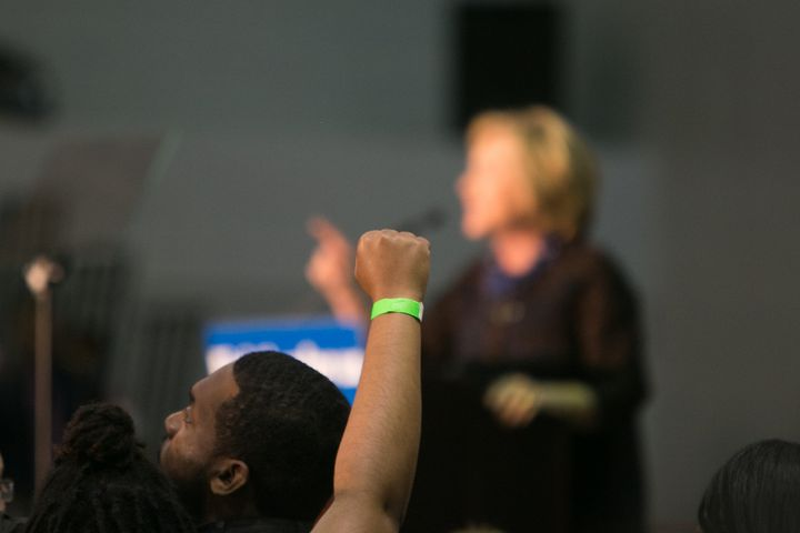 "A Black Lives Matter protester throws a fist up as Clinton speaks at an ""African Americans For Hillary'' rally in Octobe"