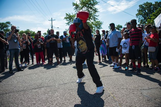 Malik Parker, 13, shadow boxes outside Ali's childhood home where mourners wait to pay their