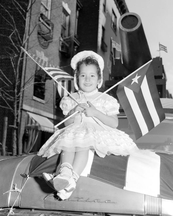 Luz Valentin, 5, has the spirit as she waves American and Puerto Rican flags from the hood of a car in the 1960 Puerto Rican
