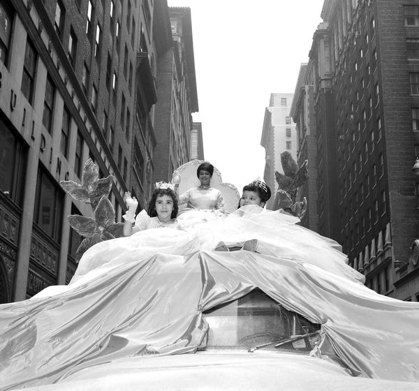 "Three women in dazzling gowns ""float"" down the parade route. <br>"