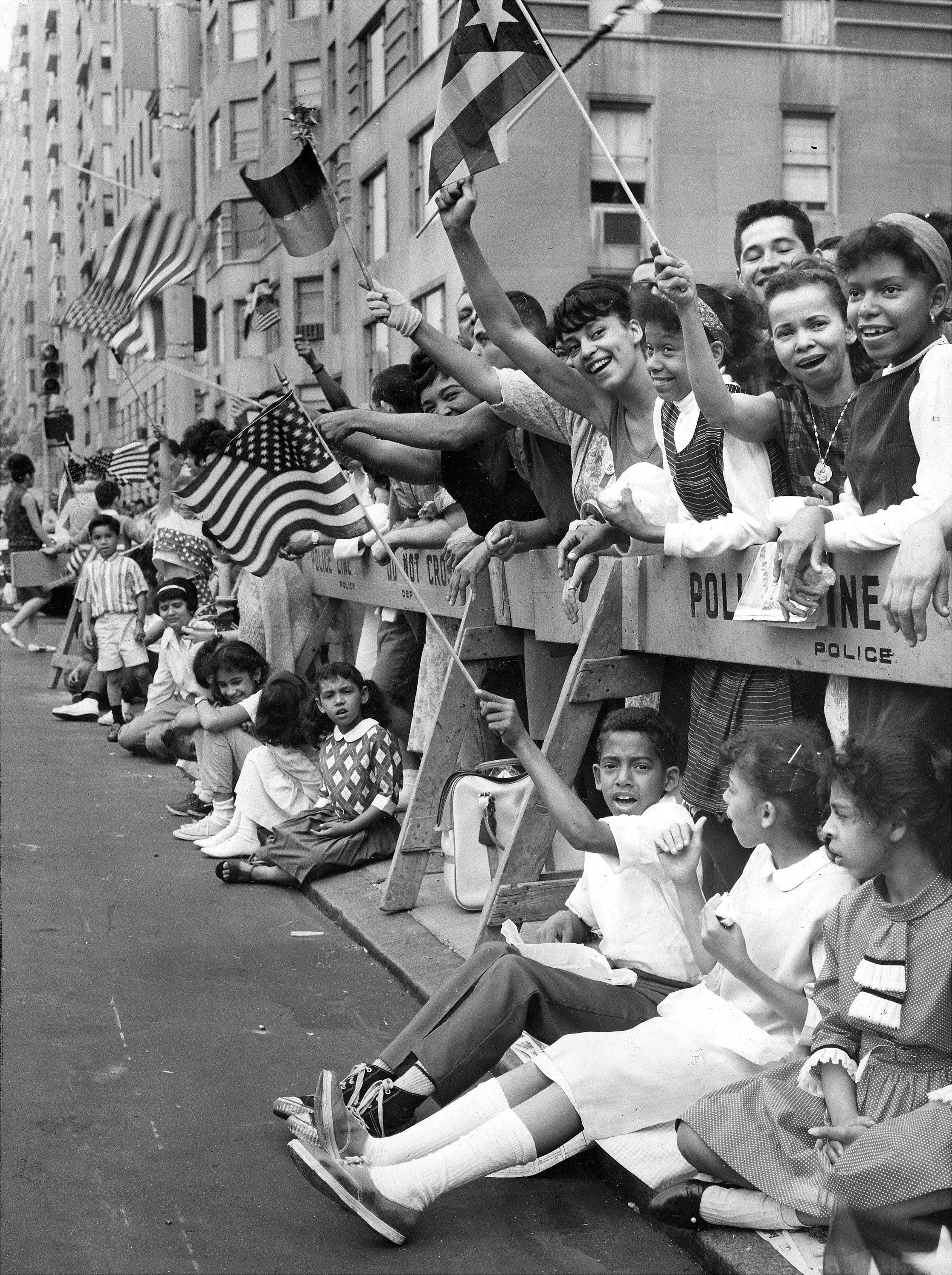 Proud spectators line Fifth Avenue and 66th Street.