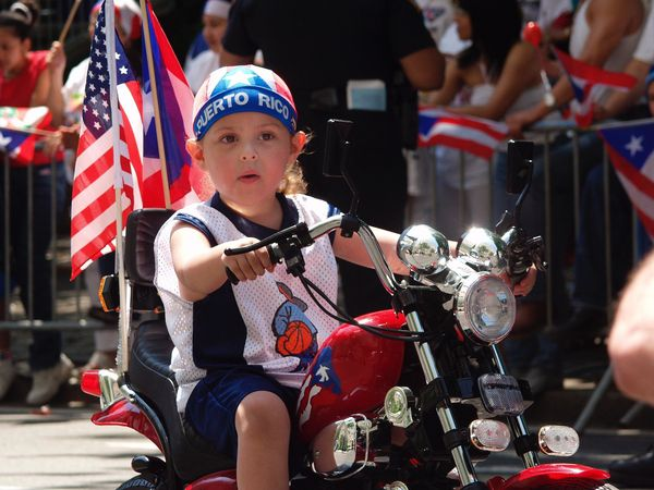 A young boy rides down the parade route on his mini-motorcycle.