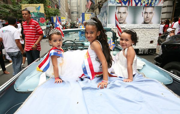 Three young girls ride in the back of a blue car along the parade route.