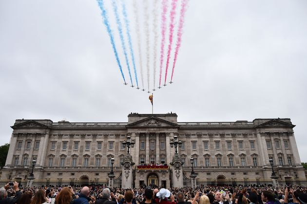 Members of the royal family line the balcony of Buckingham Palace as the Red Arrows perform a