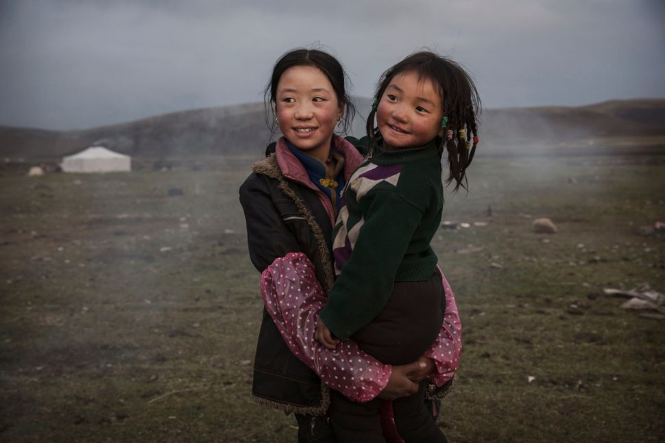 A young Tibetan nomad holds her sister at a temporary camp for cordycep fungus harvesters near Sershul on May 22, 2016.