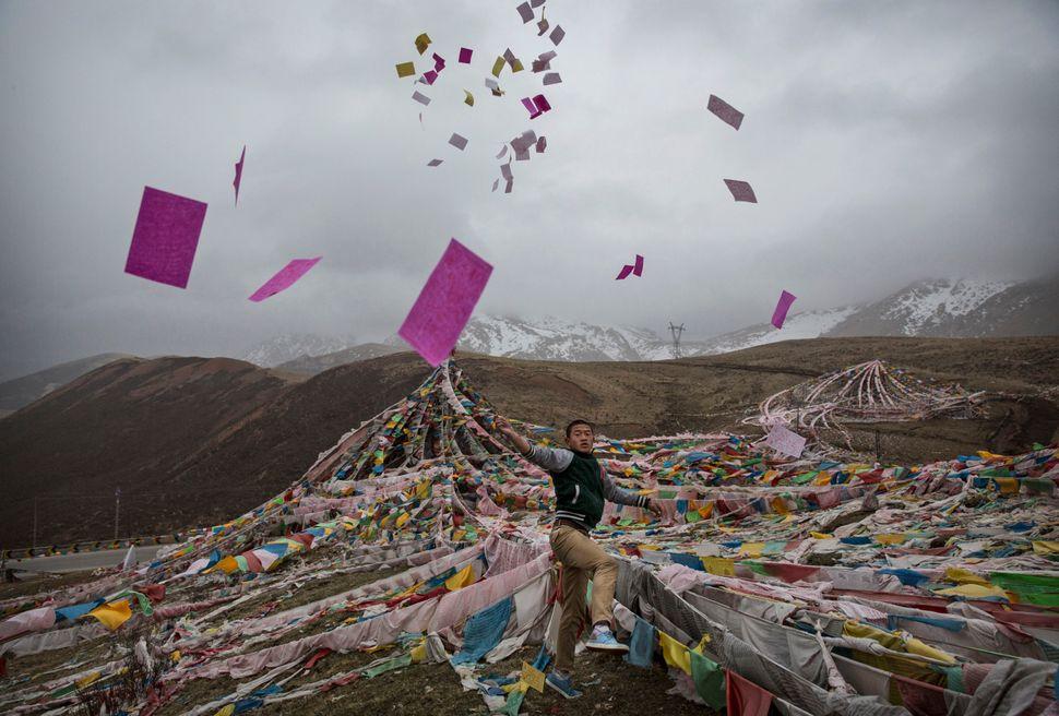 A Tibetan man throws prayers in the air at a high pass near Yushu onMay 22, 2016.