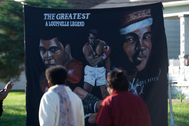 People walk in front of a banner in front of the boyhood home of Muhammad Ali on Grand Avenue before the passing of the funer