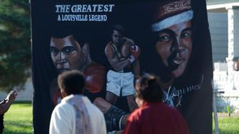 Jun 10, 2016; Louisville, KY, USA; People walk in front of a banner in front of the boyhood home of Muhammad Ali on Grand Avenue before the passing of the funeral processional. Mandatory Credit: Joshua Lindsey-USA TODAY Sports