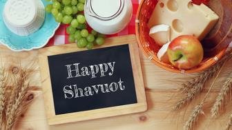 image of dairy products and fruits next to blackboard with the phrase: HAPPY SHAVUOT, on wooden background. Symbols of jewish holiday - Shavuot