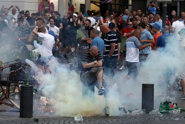 A tear gas canister explodes under a football fan as England fans clash with police on June 10, 2016...