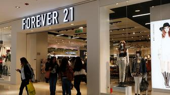 Customers walk and stand outside the first Forever 21 retail store in Lima, at Real Plaza Salaverry shopping mall October 1, 2014. Forever 21 opened its first store in Lima on September 27.  REUTERS/Mariana Bazo   (PERU - Tags: FASHION BUSINESS)