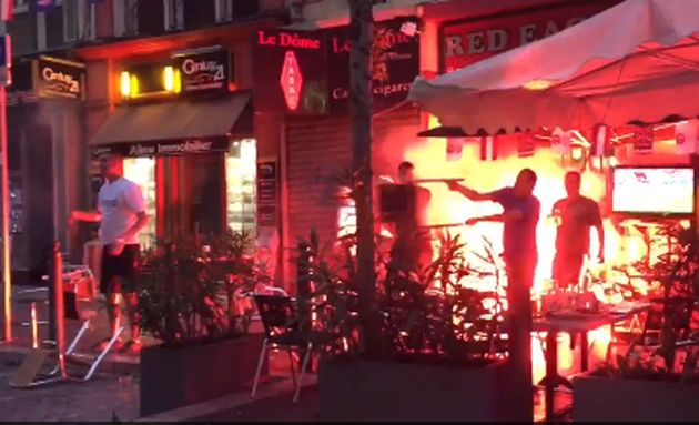 Aflare burns and a man throws a chair at the Red Eagle Cafe in the Rue de la Republique,