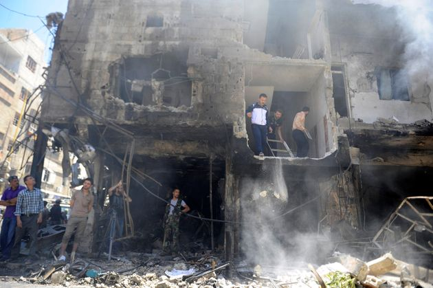 People look at the damageafter a suicide and car bomb attack in south Damascus Shi'ite suburb of...
