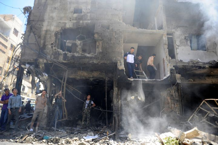 People look at the damageafter a suicide and car bomb attack in south Damascus Shi'ite suburb of Sayeda Zeinab.