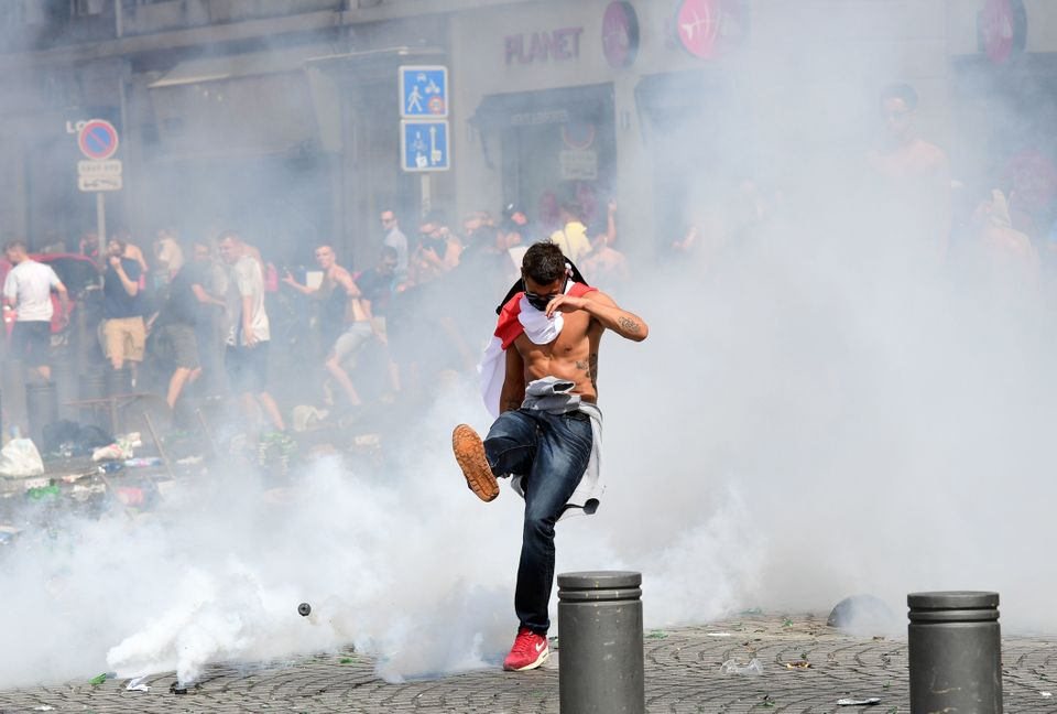 An England fan kicks away a tear gas canister after tear gas was released by French police in the city...