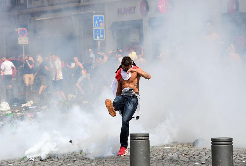 An England fan kicks away a tear gas canister after tear gas was released by French police in the city of Marseille, southern