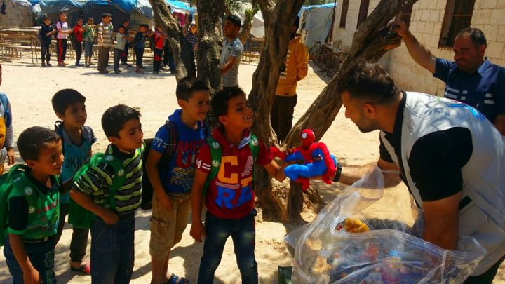 Adham hands out toys at the Atma refugee camp.
