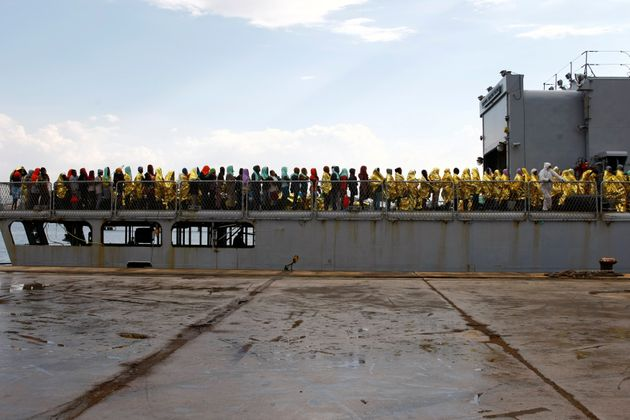 Migrants disembark from the Italian Navy vessel Aviere in the Sicilian harbour of Augusta, Italy, June...