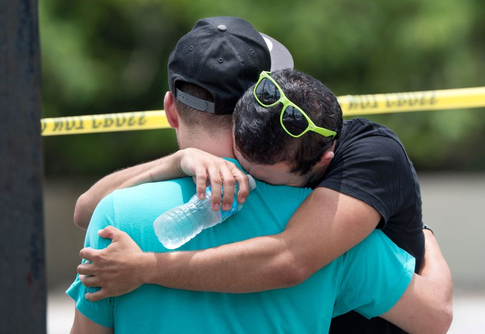 Supported by a friend, a man weeps for victims of the mass shooting just a block from the scene in Orlando, Florida, on June