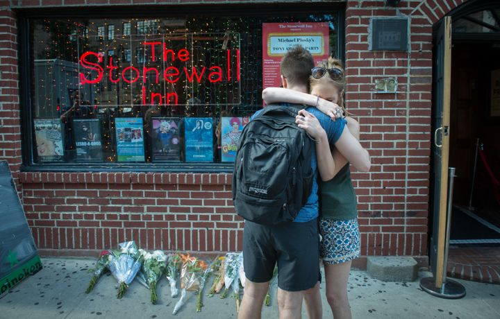 In reaction to the mass shooting, people hug outside the Stonewall Inn near a vigil for the victims.