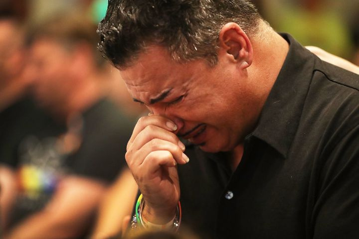 A man who was injured in the mass shooting at Pulse nightclub cries as he attends a memorial service at the Joy Metropol
