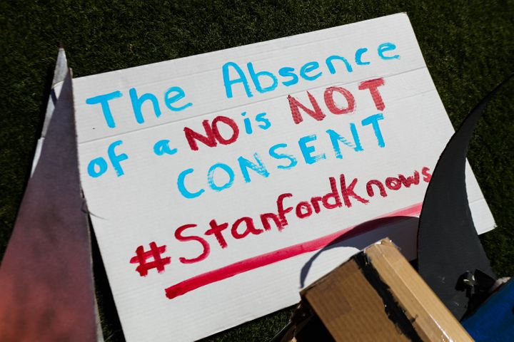Signs against protecting rapist are seen during the commencement ceremony at Stanford University, in Palo Alto, California, o