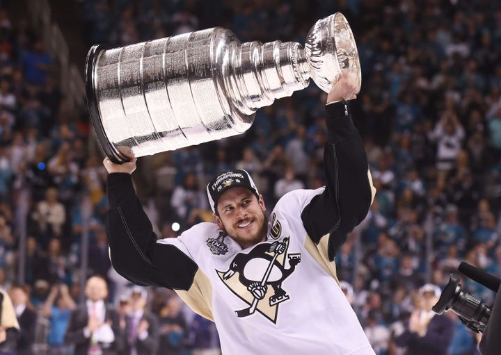 Pittsburgh Penguins center Sidney Crosby hoists the Stanley Cup after defeating the San Jose Sharks in game six.