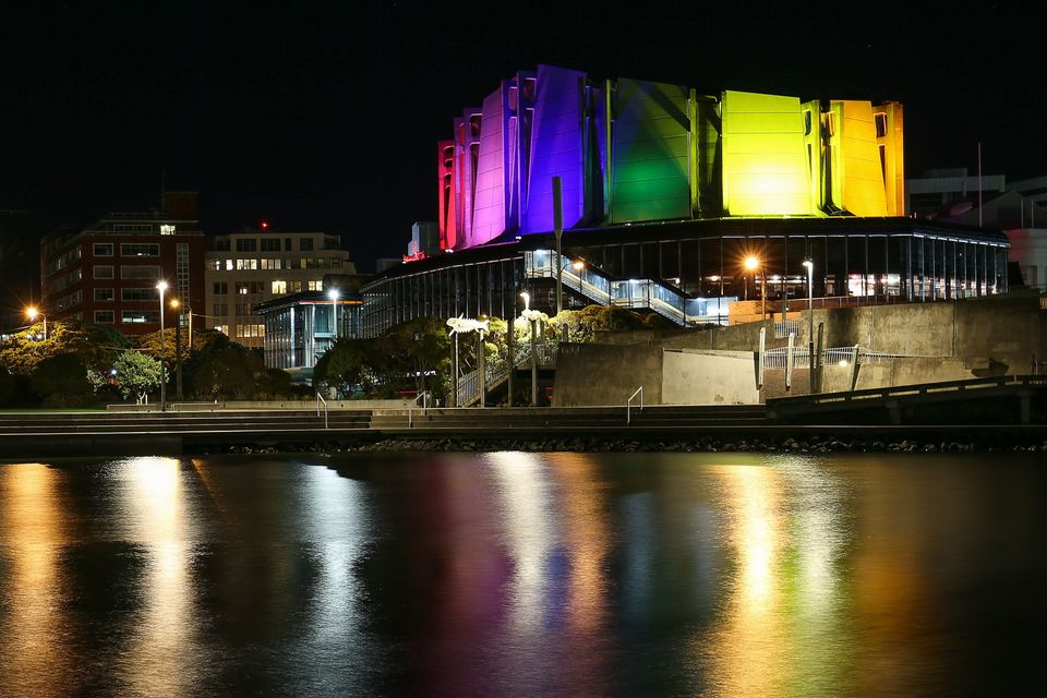 The Michael Fowler Centre is lit up in the colors of the rainbow flag after a candlelight vigil for the victims of the Pulse
