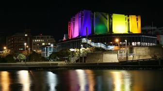 WELLINGTON, NEW ZEALAND - JUNE 13:  The Michael Fowler Centre is lit up in the colours of the rainbow flag after a candlelight vigil for the victims of the Pulse Nightclub shooting in Orlando, Florida, at Frank Kitts Park on June 13, 2016 in Wellington, New Zealand.  Omar Mateen allegedly killed more than 50 people and injured 53 others in what is the deadliest mass shootings in the country's history.  (Photo by Hagen Hopkins/Getty Images)