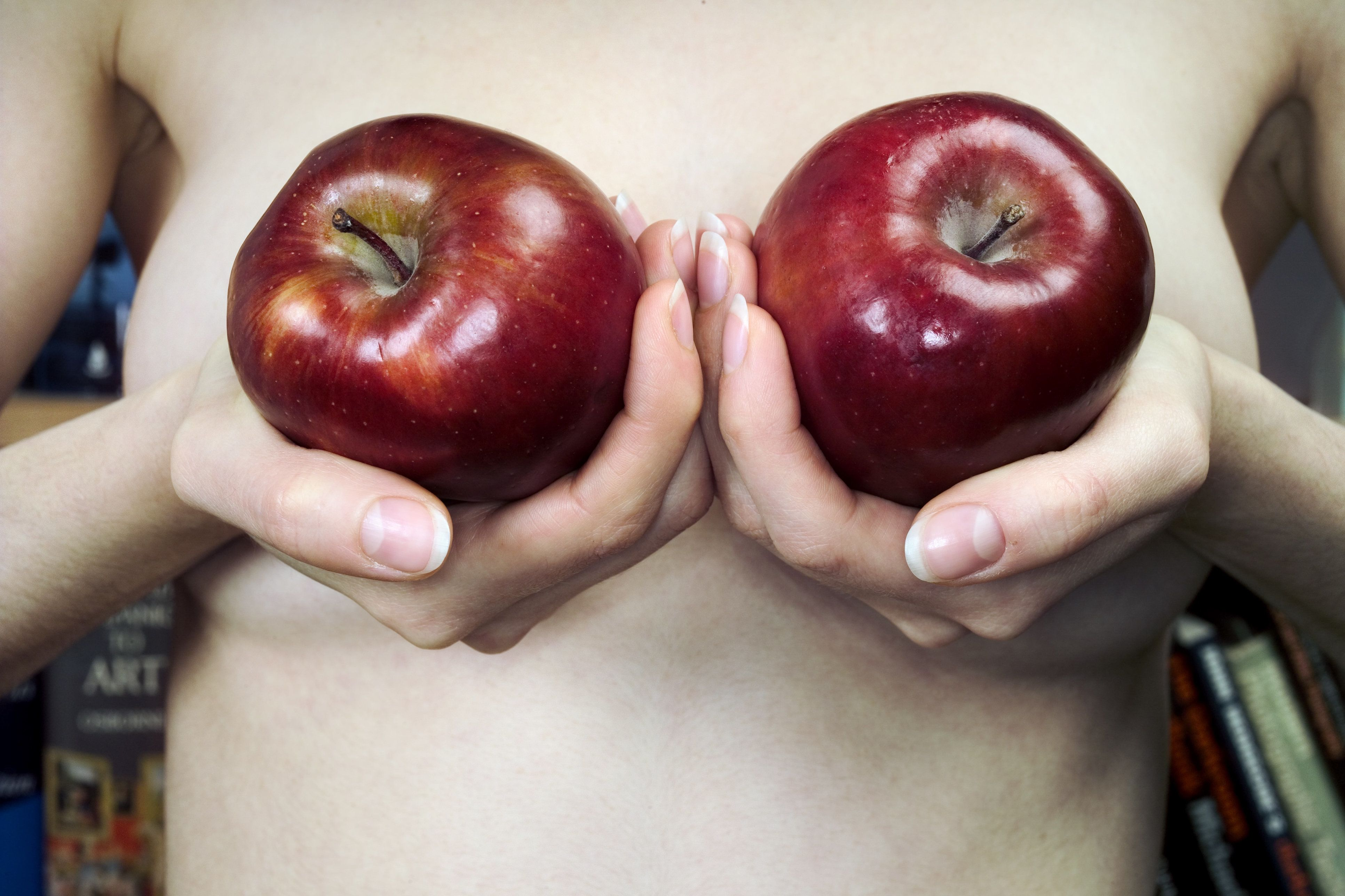 Naked female with two apples covering breasts