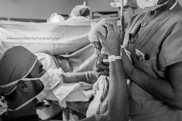 """Fathers play a very important role during C-sections. This dad provided comfort and a calming touch to his wife and his bran"