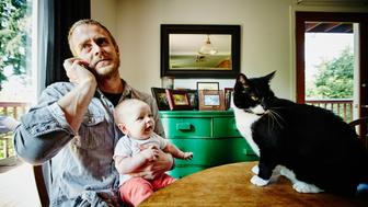 Father talking on phone while holding smiling baby looking at cat on dining table