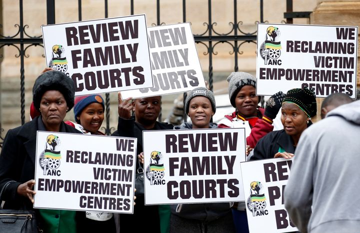 Protesters carry placards during Monday's sentencing at the Pretoria High Court, South Africa.