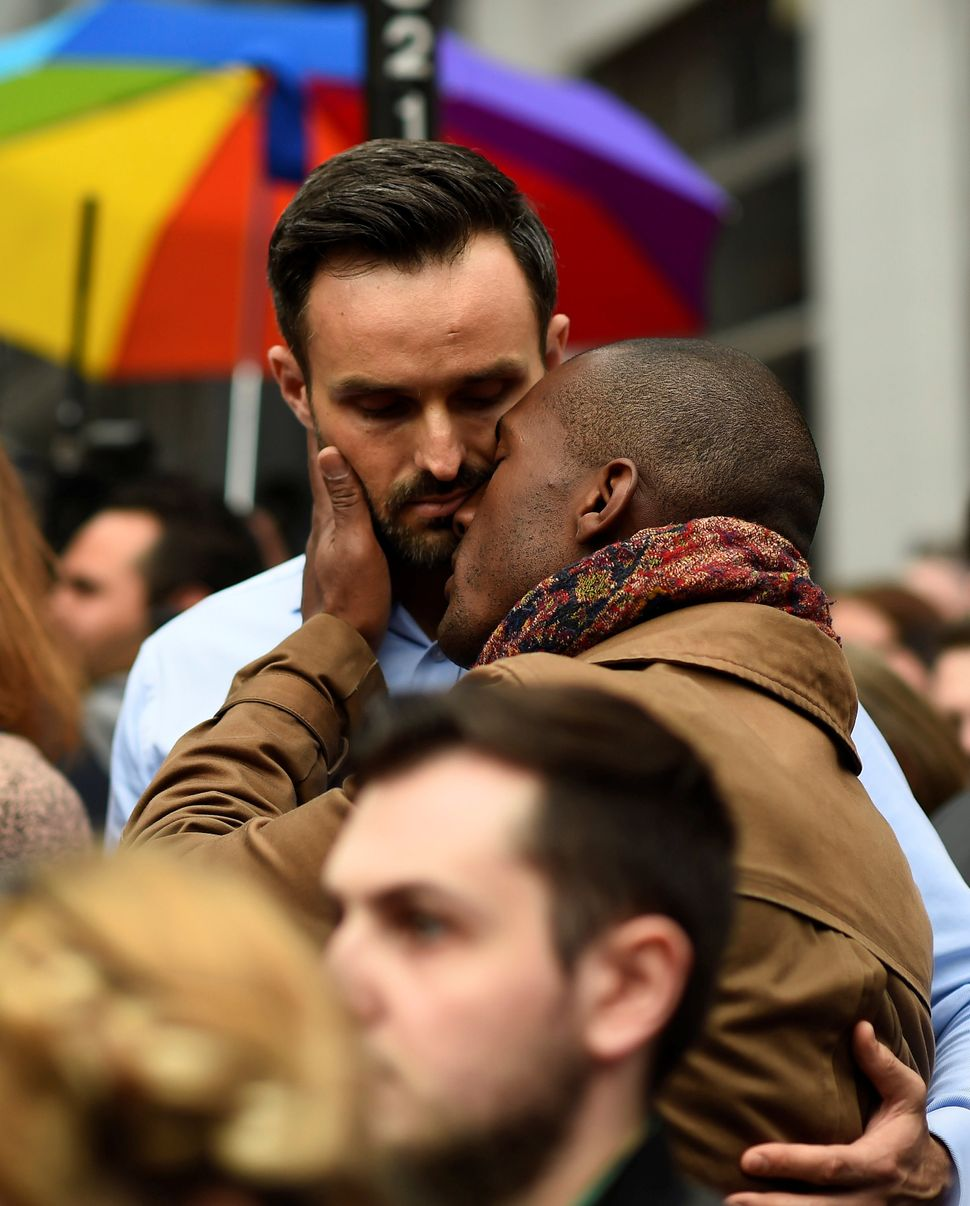 Men embrace during a minute of silence in memory of the victims of the mass shooting at a gay nightclub in Orlando.