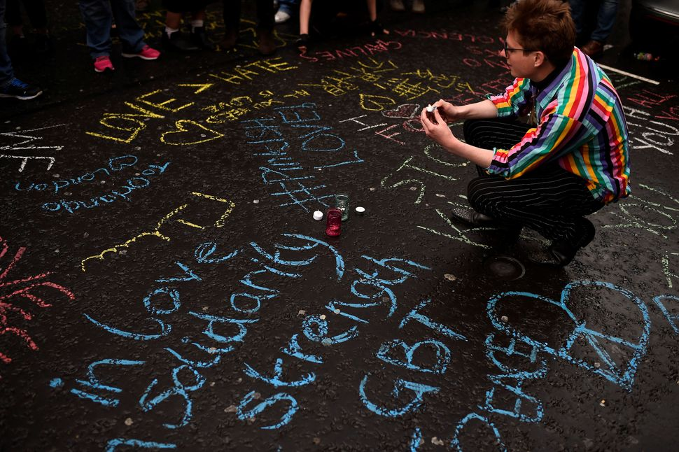 A woman kneels among graffiti in Sohohonoring the victims of the Orlando shooting.