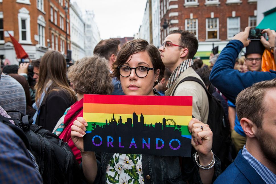 A woman holds a placard during a vigil for the victims of the Orlando nightclub shooting outside the Admiral Duncan pub on Ol