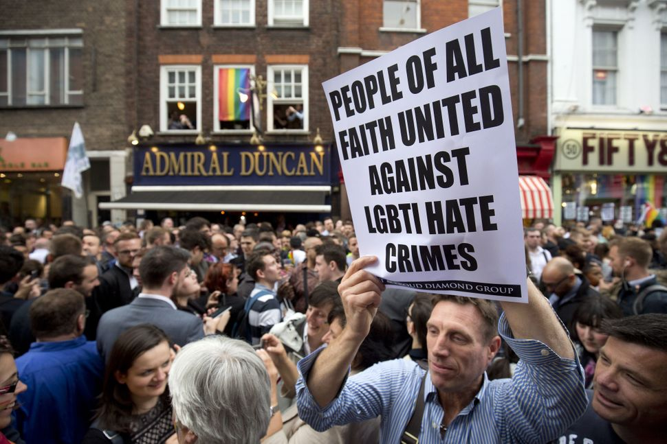 On Old Compton Street, a man holds a sign calling for religious unity against all LGBT hate crimes.
